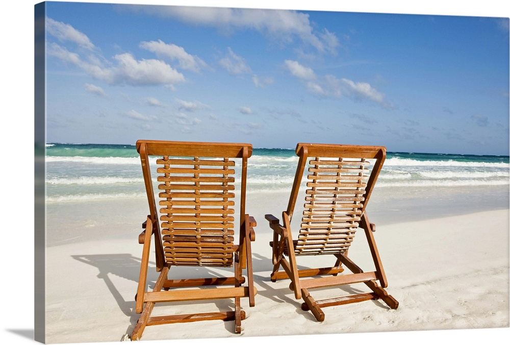 Large Solid-Faced Canvas Print Wall Art Print 30 x 20 entitled Beach chairs in the sand Solid-Faced Canvas Print entitled Beach chairs in the sand.  Large landscape photograph of two wooden lounge chairs sitting on the beach, beneath a blue sky.  Multiple sizes available.  Primary colors within this image include Brown, Silver, Dark Navy Blue.  Made in the USA.  All products come with a 365 day workmanship guarantee.  Inks used are latex-based and designed to last.  Canvas is handcrafted and made-to-order in the United States using high quality artist-grade canvas.  Archival inks prevent fading and preserve as much fine detail as possible with no over-saturation or color shifting.