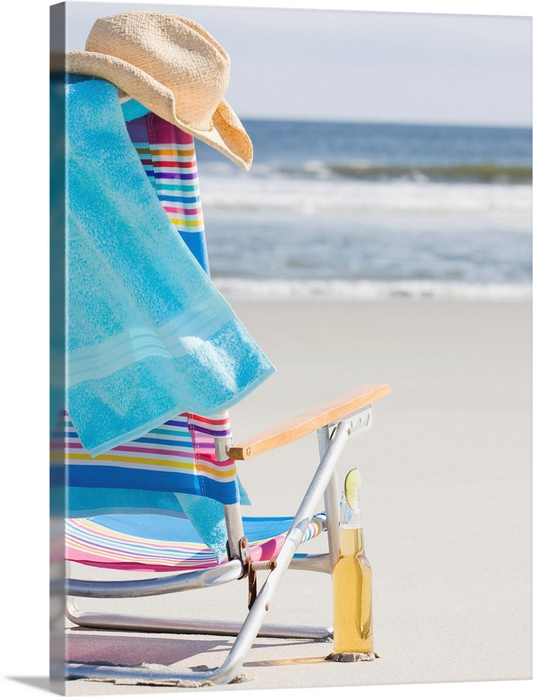 Large Solid-Faced Canvas Print Wall Art Print 30 x 40 entitled Beer next to beach chair Solid-Faced Canvas Print entitled Beer next to beach chair.  Multiple sizes available.  Primary colors within this image include Peach, White, Royal Blue, Teal.  Made in USA.  All products come with a 365 day workmanship guarantee.  Inks used are latex-based and designed to last.  Canvas depth is 1.25 and includes a finished backing with pre-installed hanging hardware.  Canvas is handcrafted and made-to-order in the United States using high quality artist-grade canvas.