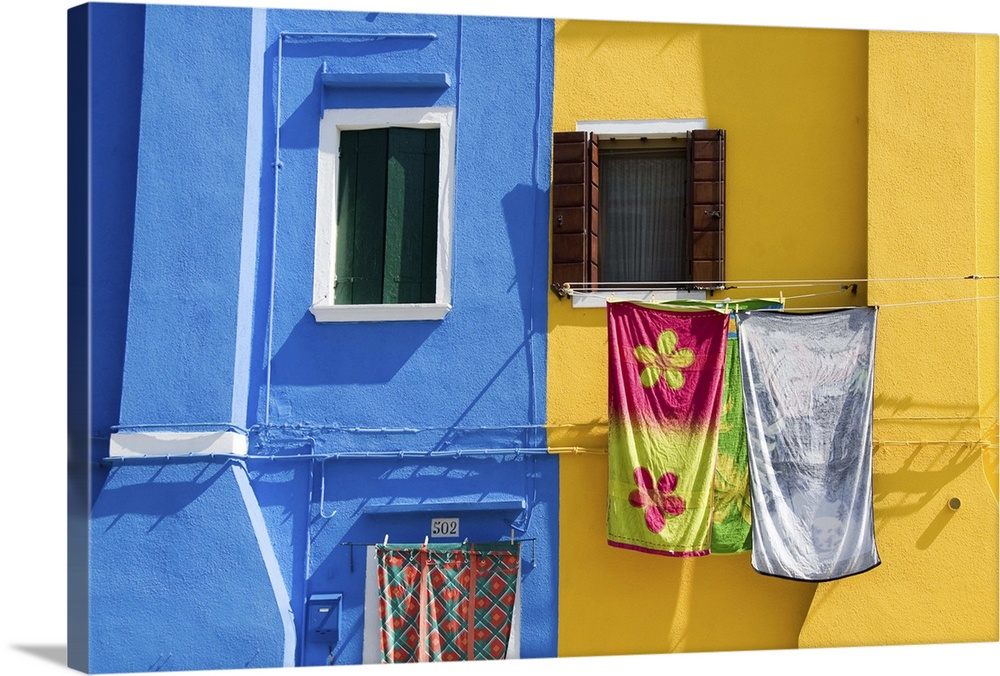 Large Gallery-Wrapped Canvas Wall Art Print 24 x 16 entitled Brightly painted houses with clothes  on a clothesline Gallery-Wrapped Canvas entitled Brightly painted houses with clothes  on a clothesline.  Venice, Burano, Veneto, Italy, Europe.  Multiple sizes available.  Primary colors within this image include Light Yellow, Muted Blue, Pale Blue, Dark Navy Blue.  Made in the USA.  Satisfaction guaranteed.  Archival-quality UV-resistant inks.  Museum-quality, artist-grade canvas mounted on sturdy wooden stretcher bars 1.5 thick.  Comes ready to hang.  Canvas is designed to prevent fading.
