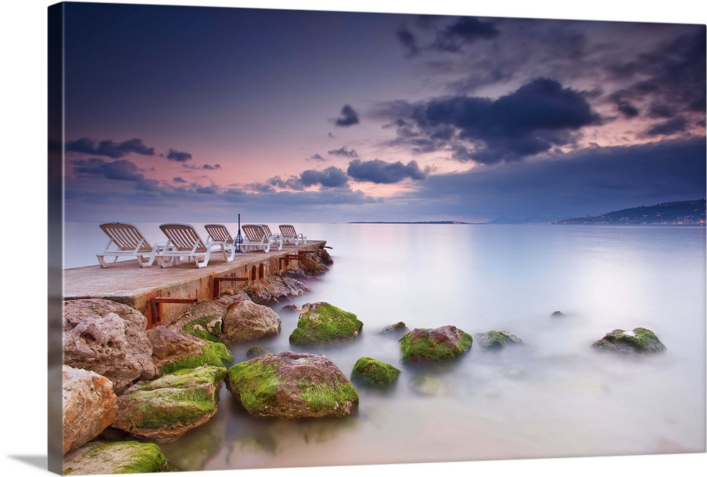 Large Solid-Faced Canvas Print Wall Art Print 30 x 20 entitled Chairs on pier with sea and clouds sky. Solid-Faced Canvas Print entitled Chairs on pier with sea and clouds sky..  Multiple sizes available.  Primary colors within this image include Brown, Dark Yellow, Silver, Muted Blue.  Made in the USA.  Satisfaction guaranteed.  Archival-quality UV-resistant inks.  Canvas is handcrafted and made-to-order in the United States using high quality artist-grade canvas.  Canvas depth is 1.25 and includes a finished backing with pre-installed hanging hardware.