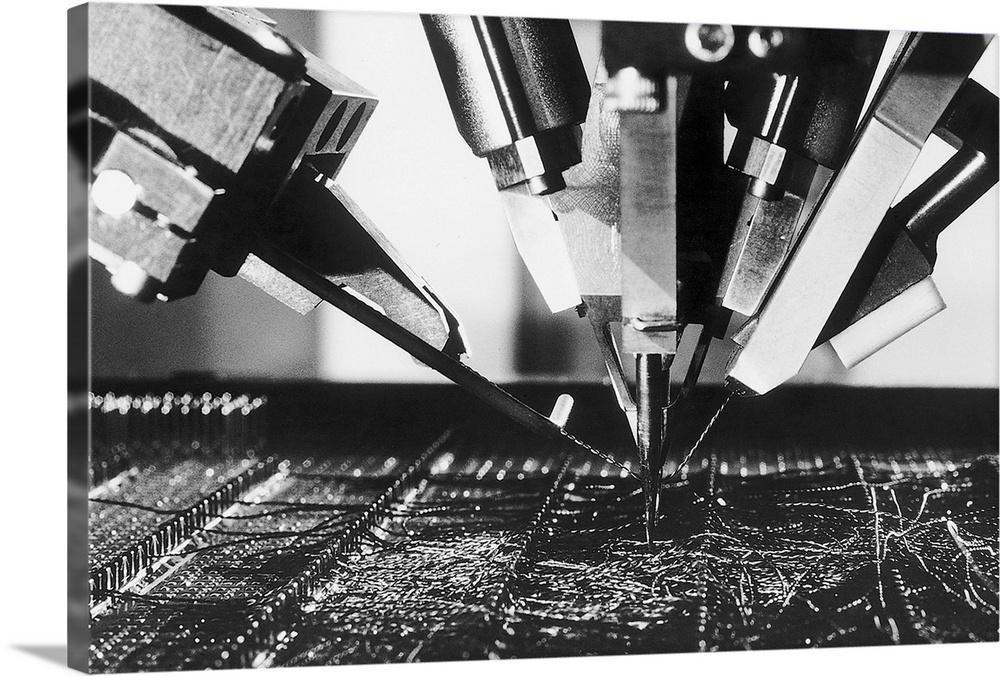 Large Solid-Faced Canvas Print Wall Art Print 30 x 20 entitled CIMPAC IBM 4300 Computer Chip Manufacturing, Atlanta, GA, 1979 Solid-Faced Canvas Print entitled CIMPAC IBM 4300 Computer Chip Manufacturing, Atlanta, GA, 1979.  7101979-Atlanta, Georgia- Like a futuristic space fighter ready to zap a target on a faraway planet, a computer-guided machine electronically spots circuit connections used in the manufacture of IBM 4300 processors. Called CIMPAC, for Computer Integrated Manufacturing Process Analysis and Control, the process pinpoints circuit junctions and automatically solders into place wires finer than a human hair.  Multiple sizes available.  Primary colors within this image include Dark Gray, Gray, White.  Made in USA.  All products come with a 365 day workmanship guarantee.  Inks used are latex-based and designed to last.  Featuring a proprietary design, our canvases produce the tightest corners without any bubbles, ripples, or bumps and will not warp or sag over time.  Archival inks prevent fading and preserve as much fine detail as possible with no over-saturation or color shifting.
