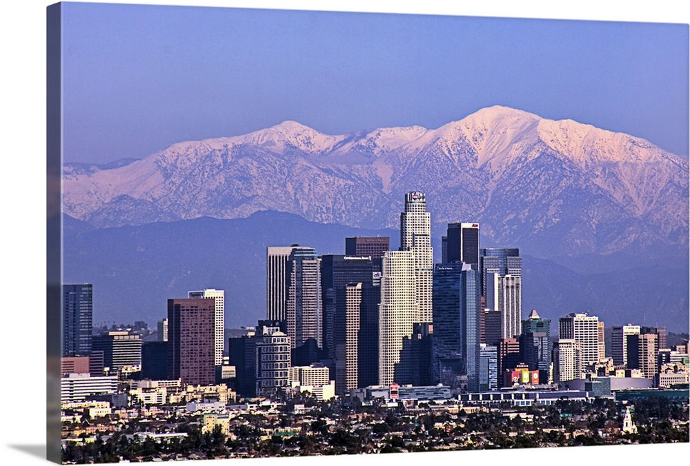 Large Solid-Faced Canvas Print Wall Art Print 30 x 20 entitled Cityscape view of Los Angeles winter time. Solid-Faced Canvas Print entitled Cityscape view of Los Angeles winter time..  This large piece is a photograph large buildings in Los Angeles with big snow covered mountains in the backdrop.  Multiple sizes available.  Primary colors within this image include Sky Blue, White, Dark Navy Blue.  Made in the USA.  All products come with a 365 day workmanship guarantee.  Archival-quality UV-resistant inks.  Featuring a proprietary design, our canvases produce the tightest corners without any bubbles, ripples, or bumps and will not warp or sag over time.  Canvas depth is 1.25 and includes a finished backing with pre-installed hanging hardware.