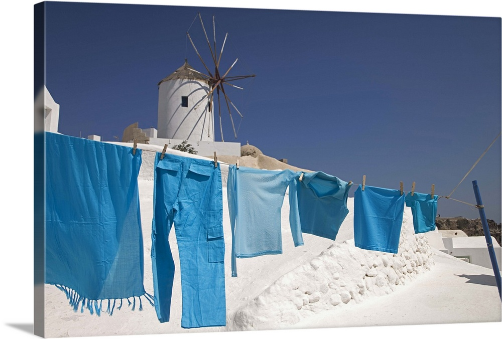 Large Gallery-Wrapped Canvas Wall Art Print 24 x 16 entitled Clothes hanging to dry near a windmill in Oia, Santorini, Greece Gallery-Wrapped Canvas entitled Clothes hanging to dry near a windmill in Oia, Santorini, Greece.  Greece, Santorini, Oia, clothes drying, windmill in background.  Multiple sizes available.  Primary colors within this image include Black, Gray, White, Muted Blue.  Made in USA.  Satisfaction guaranteed.  Archival-quality UV-resistant inks.  Canvas is acid-free and 20 millimeters thick.  Canvas frames are built with farmed or reclaimed domestic pine or poplar wood.