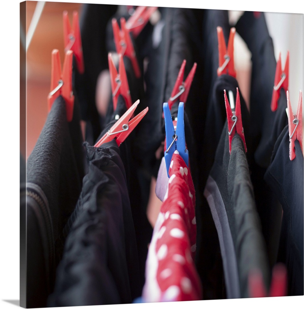 Large Gallery-Wrapped Canvas Wall Art Print 16 x 16 entitled Clothespins on clothes Gallery-Wrapped Canvas entitled Clothespins on clothes.  Dark laundry hanging to dry, with one colorful piece amongst.  Multiple sizes available.  Primary colors within this image include Dark Red, Pink, Black, Silver.  Made in USA.  All products come with a 365 day workmanship guarantee.  Archival-quality UV-resistant inks.  Canvas frames are built with farmed or reclaimed domestic pine or poplar wood.  Canvas is a 65 polyester, 35 cotton base, with two acrylic latex primer basecoats and a semi-gloss inkjet receptive topcoat.