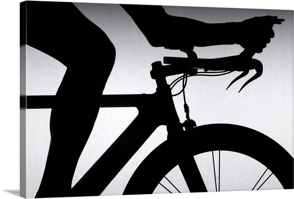 Large Solid-Faced Canvas Print Wall Art Print 30 x 20 entitled Cyclist with time trial bicycle. Solid-Faced Canvas Print entitled Cyclist with time trial bicycle..  A silhouette is shown of a cyclist only showing their leg and arm and the top front half of the bike.  Multiple sizes available.  Primary colors within this image include Black, Gray, White.  Made in the USA.  All products come with a 365 day workmanship guarantee.  Inks used are latex-based and designed to last.  Featuring a proprietary design, our canvases produce the tightest corners without any bubbles, ripples, or bumps and will not warp or sag over time.  Canvas depth is 1.25 and includes a finished backing with pre-installed hanging hardware.