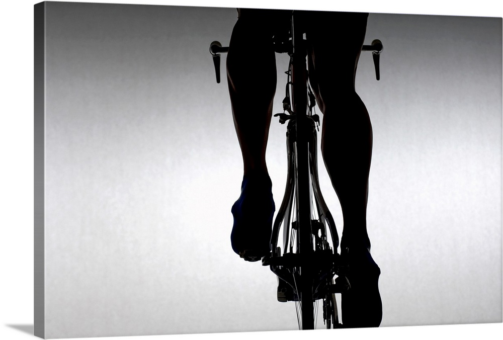Large Solid-Faced Canvas Print Wall Art Print 30 x 20 entitled Cyclist with time trial bicycle. Solid-Faced Canvas Print entitled Cyclist with time trial bicycle..  This is a wall decoration that is a monochromatic silhouette photograph of a womanos legs cycling against a blank backdrop.  Multiple sizes available.  Primary colors within this image include Black, Gray, White.  Made in the USA.  Satisfaction guaranteed.  Inks used are latex-based and designed to last.  Canvas is handcrafted and made-to-order in the United States using high quality artist-grade canvas.  Featuring a proprietary design, our canvases produce the tightest corners without any bubbles, ripples, or bumps and will not warp or sag over time.