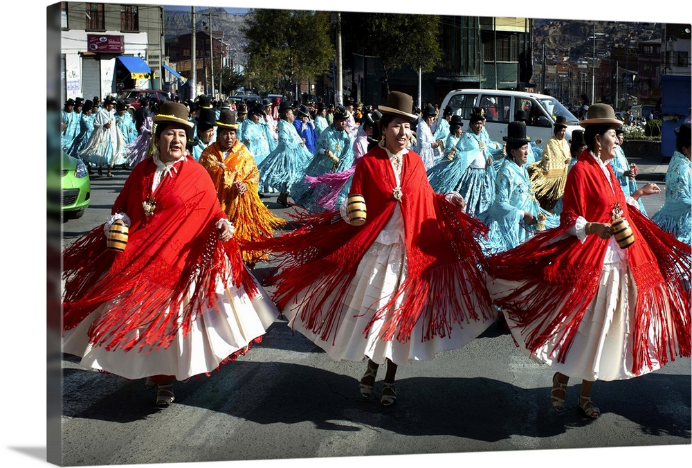 Large Gallery-Wrapped Canvas Wall Art Print 24 x 16 entitled Dancing Cholitas, La Paz, Bolivia Gallery-Wrapped Canvas entitled Dancing Cholitas, La Paz, Bolivia.  Dressed in the traditional indigenous Aymaran clothing of bowler hats, mantas or shawls and pollera dresses, cholitas dance and sway through the neighborhood of Villa Fatima in La Paz, Bolivia celebrating a religious festival.  Multiple sizes available.  Primary colors within this image include Dark Red, White, Dark Forest Green.  Made in the USA.  Satisfaction guaranteed.  Archival-quality UV-resistant inks.  Canvas is acid-free and 20 millimeters thick.  Canvases have a UVB protection built in to protect against fading and moisture and are designed to last for over 100 years.