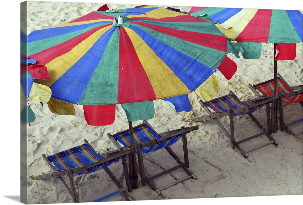Large Solid-Faced Canvas Print Wall Art Print 30 x 20 entitled Deck chairs and bright umbrellas on Sunny beach in Thailand. Solid-Faced Canvas Print entitled Deck chairs and bright umbrellas on Sunny beach in Thailand..  Multiple sizes available.  Primary colors within this image include Dark Red, Gray, White, Royal Blue.  Made in USA.  All products come with a 365 day workmanship guarantee.  Archival-quality UV-resistant inks.  Featuring a proprietary design, our canvases produce the tightest corners without any bubbles, ripples, or bumps and will not warp or sag over time.  Canvas is handcrafted and made-to-order in the United States using high quality artist-grade canvas.