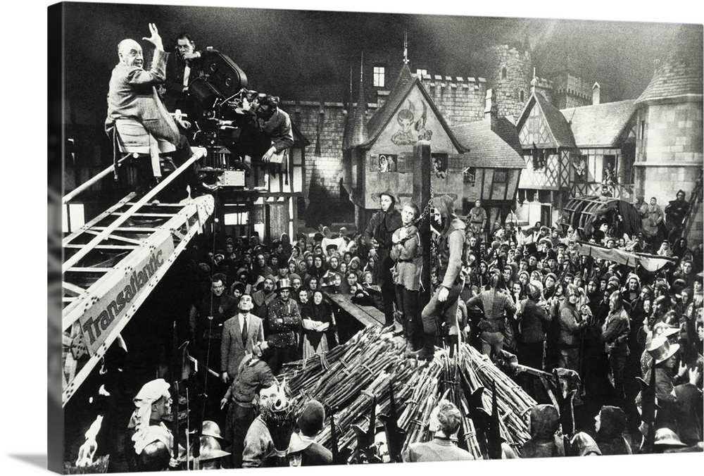 Large Solid-Faced Canvas Print Wall Art Print 30 x 20 entitled Director Otto Preminger filming a scene from Saint Joan Solid-Faced Canvas Print entitled Director Otto Preminger filming a scene from Saint Joan.  Producer-Director Otto Preminger, on camera boom, readies his crew and the crowd on a Rouen marketplace set, for the near-tragic scene in which Miss Seberg is burned at the stake.  Multiple sizes available.  Primary colors within this image include Dark Gray, White.  Made in the USA.  All products come with a 365 day workmanship guarantee.  Inks used are latex-based and designed to last.  Featuring a proprietary design, our canvases produce the tightest corners without any bubbles, ripples, or bumps and will not warp or sag over time.  Archival inks prevent fading and preserve as much fine detail as possible with no over-saturation or color shifting.