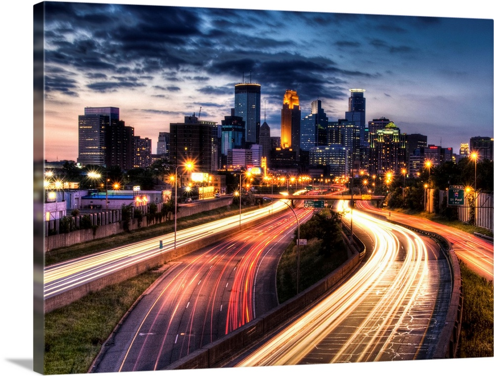Large Gallery-Wrapped Canvas Wall Art Print 24 x 17 entitled Downtown Minneapolis skyline and light trails on road Gallery-Wrapped Canvas entitled Downtown Minneapolis skyline and light trails on road.  Giant photograph depicts a busy city filled with skyscrapers and highways brightly lit at night.  Photographer uses a slow shutter speed on the camera to get the effect of the fast moving lights on the cars.  Multiple sizes available.  Primary colors within this image include Peach Light Yellow Black White.  Made in the USA.  All products come with a 365 day workmanship guarantee.  Archival-quality UV-resistant inks.  Canvas is acid-free and 20 millimeters thick.  Canvases have a UVB protection built in to protect against fading and moisture and are designed to last for over 100 years.