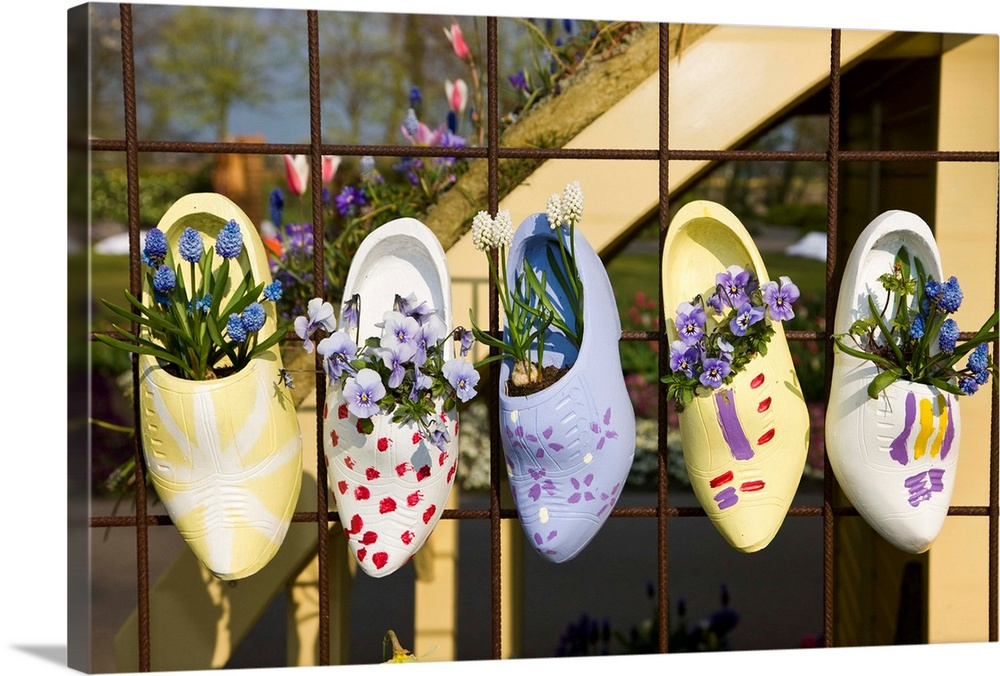 Large Solid-Faced Canvas Print Wall Art Print 30 x 20 entitled Dutch Wooden Shoes With Flowers Hanging In Keukenhof Gardens Solid-Faced Canvas Print entitled Dutch Wooden Shoes With Flowers Hanging In Keukenhof Gardens.  Multiple sizes available.  Primary colors within this image include Brown, Peach, Black, Pale Blue.  Made in USA.  All products come with a 365 day workmanship guarantee.  Inks used are latex-based and designed to last.  Featuring a proprietary design, our canvases produce the tightest corners without any bubbles, ripples, or bumps and will not warp or sag over time.  Canvas is handcrafted and made-to-order in the United States using high quality artist-grade canvas.