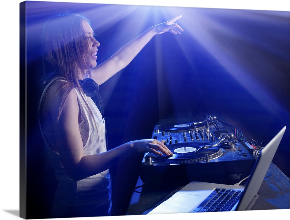 Large Gallery-Wrapped Canvas Wall Art Print 24 x 18 entitled Female DJ in Nightclub Reaching Out to Audience Gallery-Wrapped Canvas entitled Female DJ in Nightclub Reaching Out to Audience.  Female DJ using decks and laptop, reaching out to audience, surrounded by bright lights.  Multiple sizes available.  Primary colors within this image include Dark Blue, Pale Blue, Royal Blue, Dark Navy Blue.  Made in USA.  All products come with a 365 day workmanship guarantee.  Inks used are latex-based and designed to last.  Canvas is a 65 polyester, 35 cotton base, with two acrylic latex primer basecoats and a semi-gloss inkjet receptive topcoat.  Museum-quality, artist-grade canvas mounted on sturdy wooden stretcher bars 1.5 thick.  Comes ready to hang.