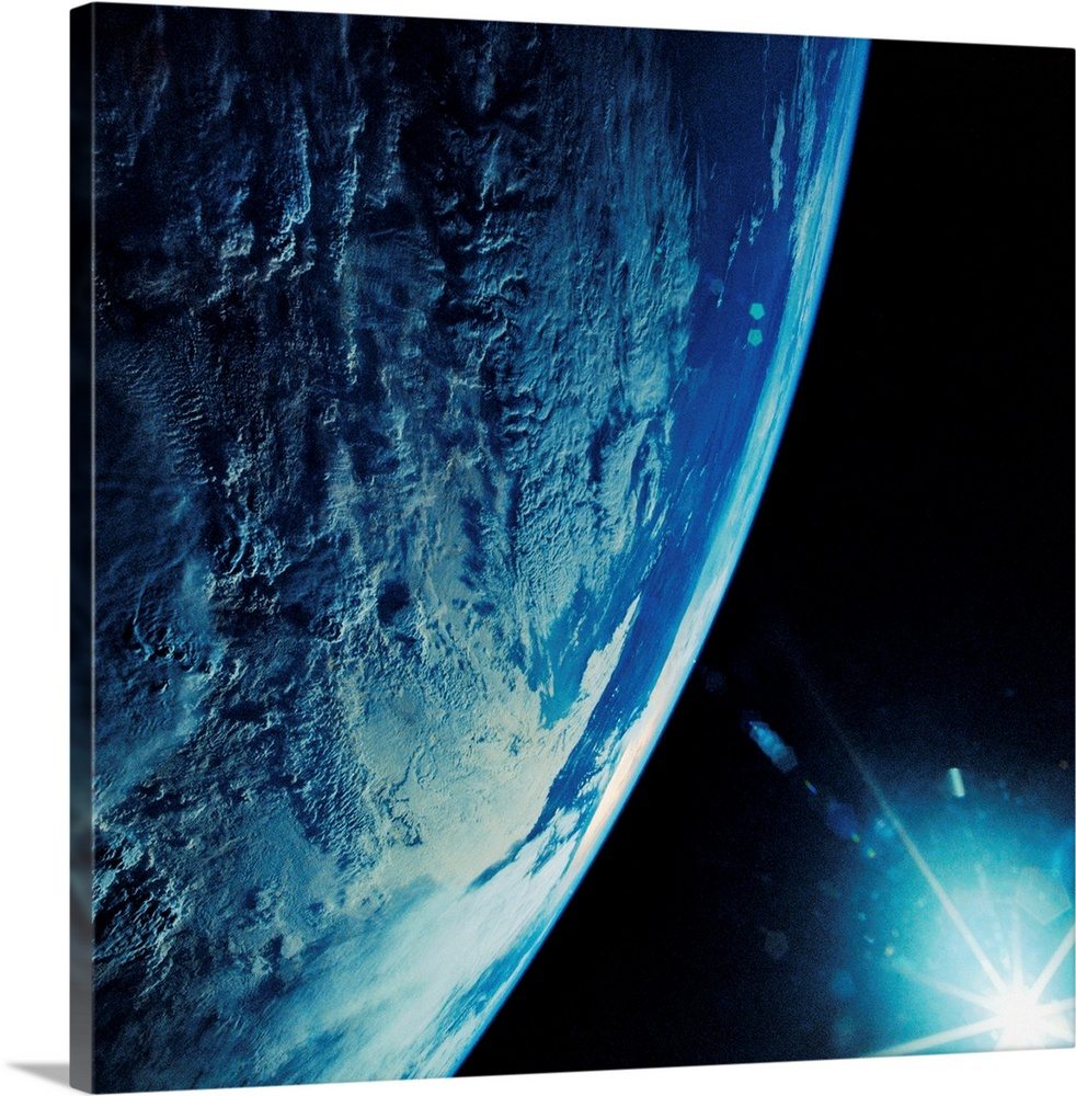 Large Solid-Faced Canvas Print Wall Art Print 20 x 20 entitled Florida Peninsula From Discovery Solid-Faced Canvas Print entitled Florida Peninsula From Discovery.  Earth curvature displays the Florida Peninsula under cloud cover with sun starburst, taken with a Hasselblad camera on board the Discovery.  Multiple sizes available.  Primary colors within this image include Black, White, Royal Blue, Teal.  Made in USA.  All products come with a 365 day workmanship guarantee.  Inks used are latex-based and designed to last.  Featuring a proprietary design, our canvases produce the tightest corners without any bubbles, ripples, or bumps and will not warp or sag over time.  Archival inks prevent fading and preserve as much fine detail as possible with no over-saturation or color shifting.
