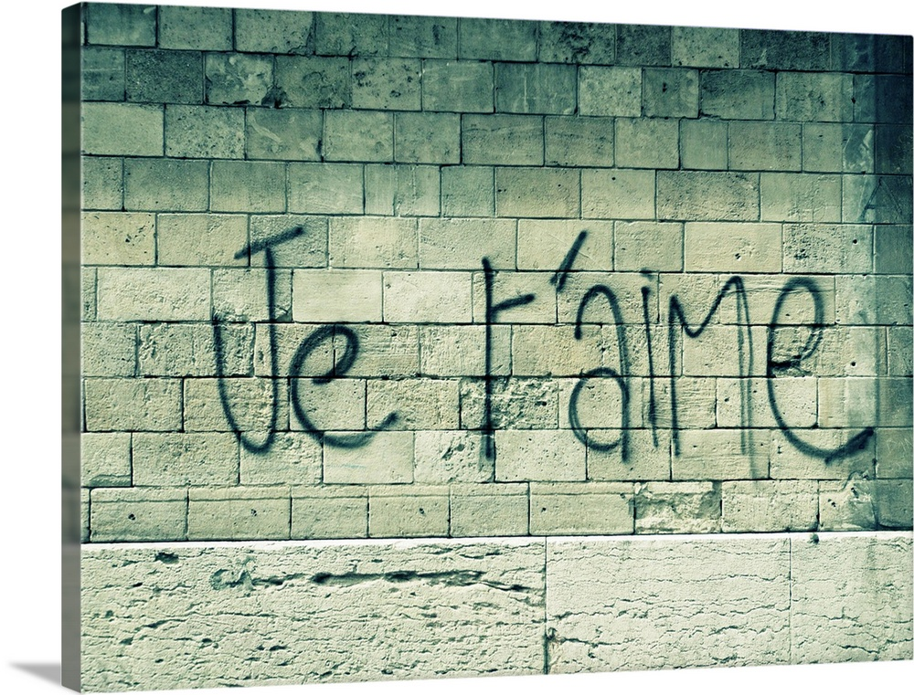 Large Solid-Faced Canvas Print Wall Art Print 40 x 30 entitled Graffiti on a wall in Paris reads 'Je t'aime' or 'I love yo... Solid-Faced Canvas Print entitled Graffiti on a wall in Paris reads Je taime or I love you in English..  Big canvas photo of a stone wall with the words I love you in French sprayed painted on it.  Multiple sizes available.  Primary colors within this image include Black, Gray, Silver.  Made in the USA.  Satisfaction guaranteed.  Inks used are latex-based and designed to last.  Archival inks prevent fading and preserve as much fine detail as possible with no over-saturation or color shifting.  Featuring a proprietary design, our canvases produce the tightest corners without any bubbles, ripples, or bumps and will not warp or sag over time.