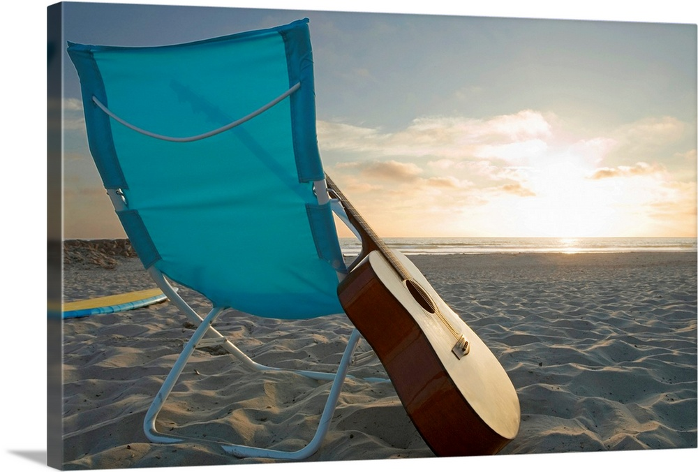 Large Solid-Faced Canvas Print Wall Art Print 30 x 20 entitled Guitar in lounge chair on beach Solid-Faced Canvas Print entitled Guitar in lounge chair on beach.  Multiple sizes available.  Primary colors within this image include Dark Gray, Gray, White, Gray Blue.  Made in the USA.  All products come with a 365 day workmanship guarantee.  Archival-quality UV-resistant inks.  Canvas is handcrafted and made-to-order in the United States using high quality artist-grade canvas.  Canvas depth is 1.25 and includes a finished backing with pre-installed hanging hardware.