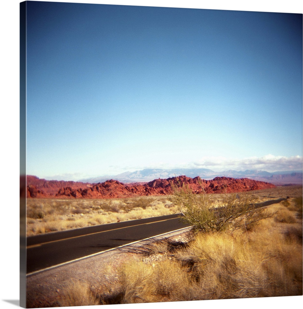 Large Solid-Faced Canvas Print Wall Art Print 20 x 20 entitled Highway entering the Valley of Fire in Nevada. Solid-Faced Canvas Print entitled Highway entering the Valley of Fire in Nevada..  Photo of the highway entering the Valley of Fire in Nevada.  Near Las Vegas.  Red rocks.  Desert. Holga.  Toy camera.  Multiple sizes available.  Primary colors within this image include Peach, White, Dark Forest Green, Gray Blue.  Made in the USA.  Satisfaction guaranteed.  Inks used are latex-based and designed to last.  Featuring a proprietary design, our canvases produce the tightest corners without any bubbles, ripples, or bumps and will not warp or sag over time.  Canvas depth is 1.25 and includes a finished backing with pre-installed hanging hardware.