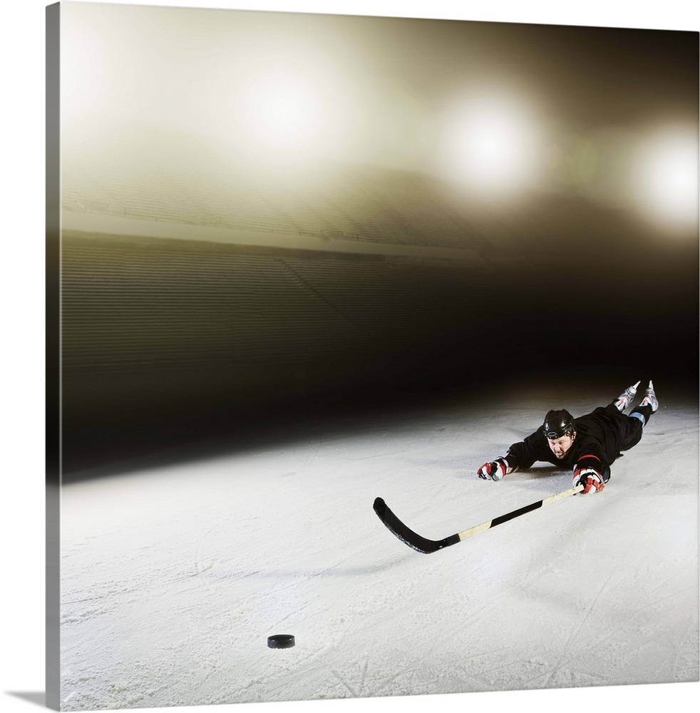 Large Gallery-Wrapped Canvas Wall Art Print 16 x 16 entitled Ice hockey player diving for puck Gallery-Wrapped Canvas entitled Ice hockey player diving for puck.  Stadium, cold, ice, ice hockey stick, light flare, skates, sports clothing, protective clothing, competition, ice rink, yellow, orange, sliding, stretching.  Multiple sizes available.  Primary colors within this image include Black, Silver.  Made in the USA.  Satisfaction guaranteed.  Archival-quality UV-resistant inks.  Canvas is acid-free and 20 millimeters thick.  Canvas frames are built with farmed or reclaimed domestic pine or poplar wood.
