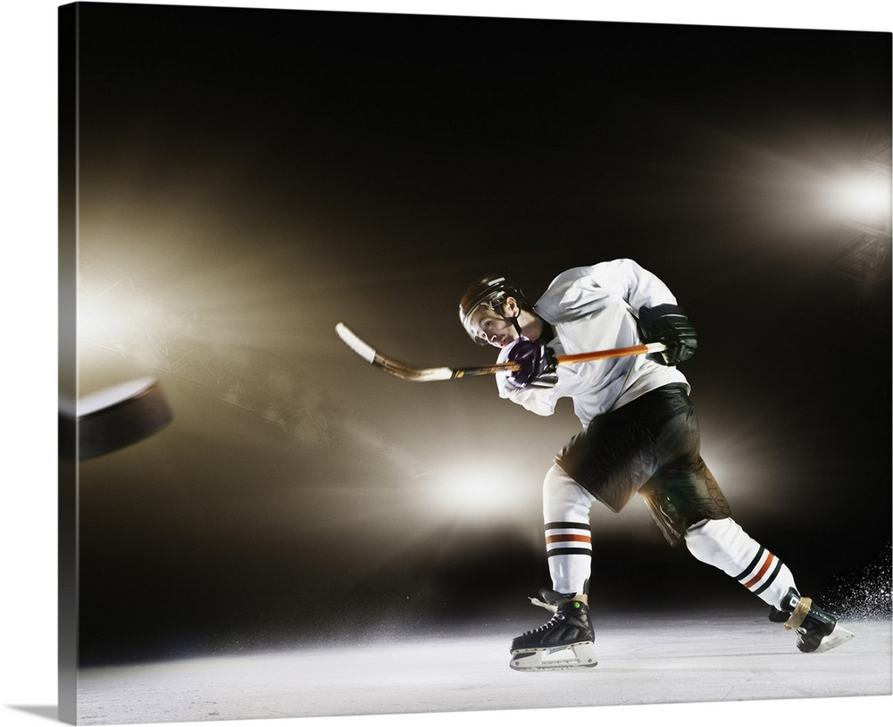 Large Gallery-Wrapped Canvas Wall Art Print 24 x 20 entitled Ice hockey player shooting puck Gallery-Wrapped Canvas entitled Ice hockey player shooting puck.  Stadium, cold, ice, ice hockey stick, light flare, skates, sports clothing, protective clothing, competition, ice rink, yellow, orange, puck, motion.  Multiple sizes available.  Primary colors within this image include Black, Gray, Silver.  Made in USA.  All products come with a 365 day workmanship guarantee.  Archival-quality UV-resistant inks.  Canvas is acid-free and 20 millimeters thick.  Museum-quality, artist-grade canvas mounted on sturdy wooden stretcher bars 1.5 thick.  Comes ready to hang.