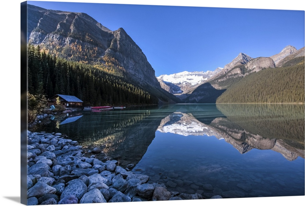 Large Solid-Faced Canvas Print Wall Art Print 30 x 20 entitled Lake Louise Boathouse, Canada Solid-Faced Canvas Print entitled Lake Louise Boathouse, Canada.  View of Lake Louise and the boathouse with reflection and shadow at the early morning.  Multiple sizes available.  Primary colors within this image include Peach, White, Royal Blue, Dark Navy Blue.  Made in USA.  All products come with a 365 day workmanship guarantee.  Inks used are latex-based and designed to last.  Canvas depth is 1.25 and includes a finished backing with pre-installed hanging hardware.  Featuring a proprietary design, our canvases produce the tightest corners without any bubbles, ripples, or bumps and will not warp or sag over time.