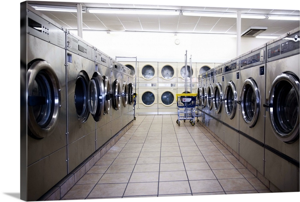 Large Solid-Faced Canvas Print Wall Art Print 30 x 20 entitled Laundromat with washers and dryers Solid-Faced Canvas Print entitled Laundromat with washers and dryers.  Multiple sizes available.  Primary colors within this image include Black, Gray, White.  Made in USA.  All products come with a 365 day workmanship guarantee.  Archival-quality UV-resistant inks.  Canvas depth is 1.25 and includes a finished backing with pre-installed hanging hardware.  Featuring a proprietary design, our canvases produce the tightest corners without any bubbles, ripples, or bumps and will not warp or sag over time.