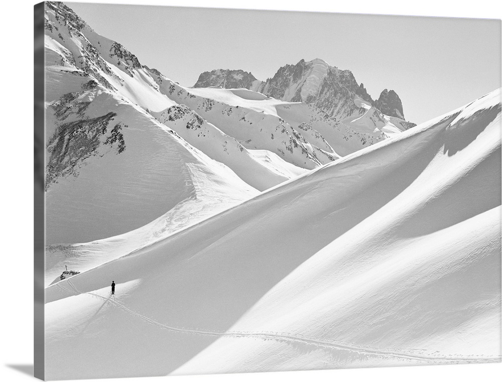 Large Solid-Faced Canvas Print Wall Art Print 40 x 30 entitled Lone Skier Shadowed by Mont Blanc, France Solid-Faced Canvas Print entitled Lone Skier Shadowed by Mont Blanc, France.  Mont Blanc, France Mont Blanc, with the slopes reaching up to the top, attracts skiers both in winter and in summer. Undated photograph.  Multiple sizes available.  Primary colors within this image include Black, Silver.  Made in USA.  Satisfaction guaranteed.  Archival-quality UV-resistant inks.  Featuring a proprietary design, our canvases produce the tightest corners without any bubbles, ripples, or bumps and will not warp or sag over time.  Archival inks prevent fading and preserve as much fine detail as possible with no over-saturation or color shifting.