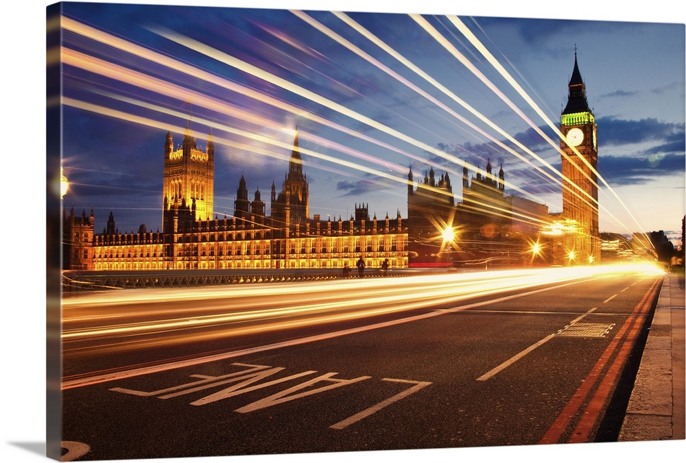 Large Solid-Faced Canvas Print Wall Art Print 30 x 20 entitled Long exposure night time shot looking towards Big Ben and t... Solid-Faced Canvas Print entitled Long exposure night time shot looking towards Big Ben and the Houses of Parliament.  Long exposure night time shot looking towards Big Ben and the Houses of Parliament, with light trails from passing London red buses.  Multiple sizes available.  Primary colors within this image include Orange, Dark Red, Light Yellow, White.  Made in the USA.  All products come with a 365 day workmanship guarantee.  Inks used are latex-based and designed to last.  Featuring a proprietary design, our canvases produce the tightest corners without any bubbles, ripples, or bumps and will not warp or sag over time.  Archival inks prevent fading and preserve as much fine detail as possible with no over-saturation or color shifting.