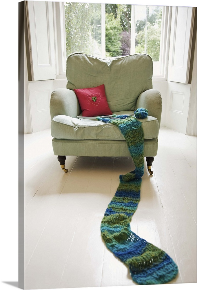 Large Solid-Faced Canvas Print Wall Art Print 20 x 30 entitled Long knitted scarf on chair Solid-Faced Canvas Print entitled Long knitted scarf on chair.  Multiple sizes available.  Primary colors within this image include Pink, Gray, White, Muted Blue.  Made in the USA.  All products come with a 365 day workmanship guarantee.  Archival-quality UV-resistant inks.  Canvas depth is 1.25 and includes a finished backing with pre-installed hanging hardware.  Featuring a proprietary design, our canvases produce the tightest corners without any bubbles, ripples, or bumps and will not warp or sag over time.