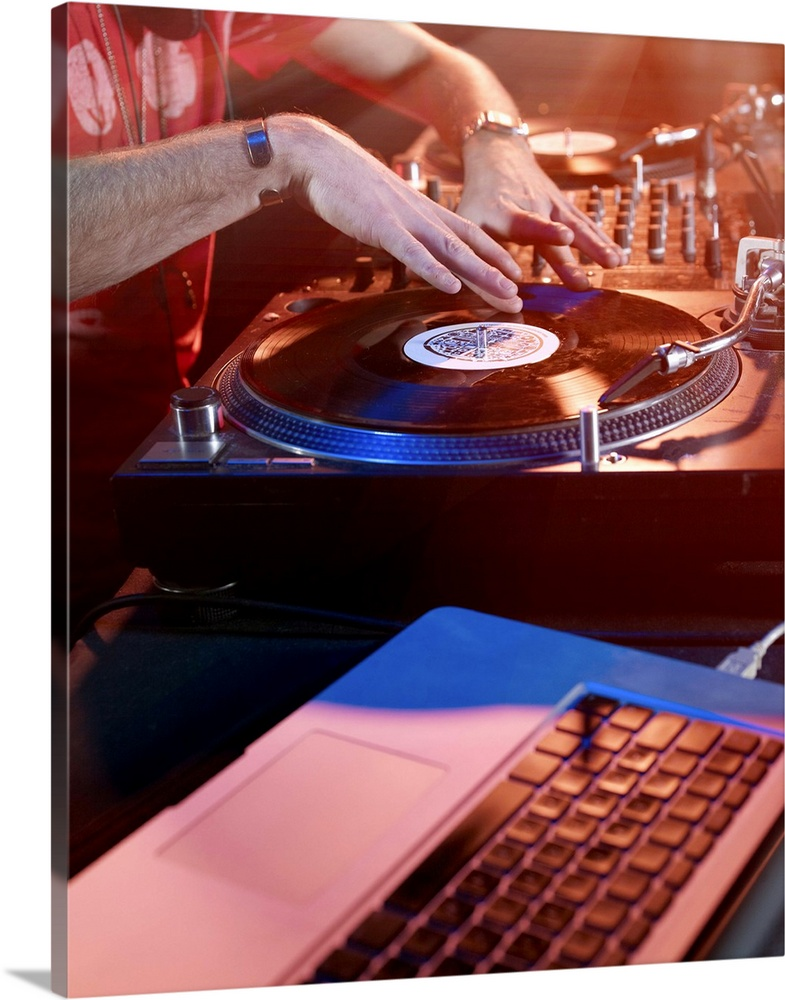 Large Gallery-Wrapped Canvas Wall Art Print 16 x 20 entitled Male DJ Using Decks and Laptop Gallery-Wrapped Canvas entitled Male DJ Using Decks and Laptop.  Close up of male DJ using decks and laptop in nightclub, surrounded by bright lights.  Multiple sizes available.  Primary colors within this image include Dark Red, Dark Blue, Sky Blue, Black.  Made in the USA.  All products come with a 365 day workmanship guarantee.  Archival-quality UV-resistant inks.  Museum-quality, artist-grade canvas mounted on sturdy wooden stretcher bars 1.5 thick.  Comes ready to hang.  Canvas is designed to prevent fading.