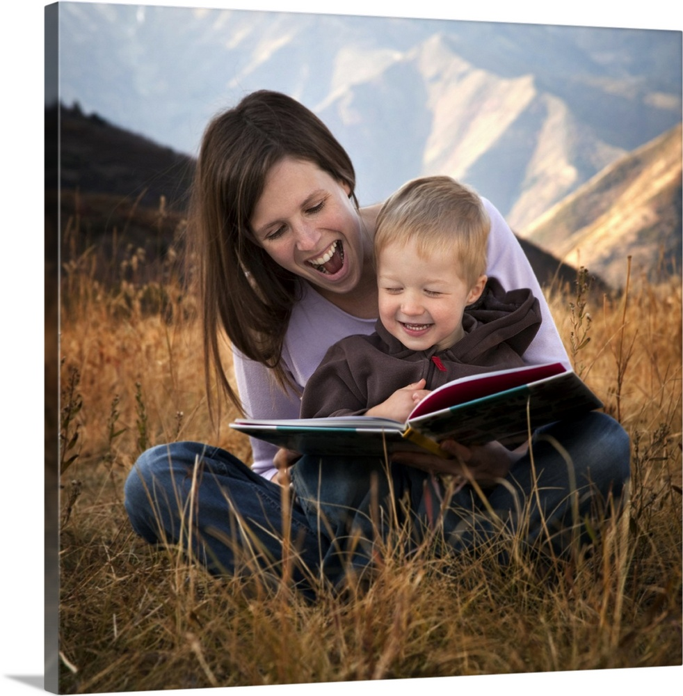 Large Gallery-Wrapped Canvas Wall Art Print 16 x 16 entitled Mother and son reading outdoors Gallery-Wrapped Canvas entitled Mother and son reading outdoors.  Multiple sizes available.  Primary colors within this image include Light Gray Dark Forest Green.  Made in USA.  Satisfaction guaranteed.  Archival-quality UV-resistant inks.  Canvases have a UVB protection built in to protect against fading and moisture and are designed to last for over 100 years.  Canvas frames are built with farmed or reclaimed domestic pine or poplar wood.