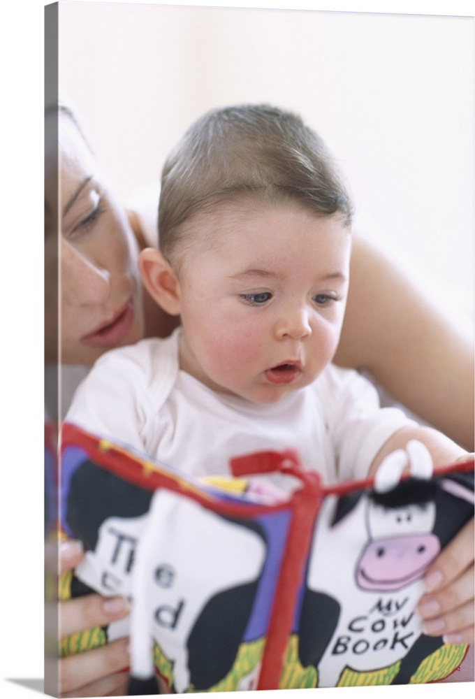 Large Gallery-Wrapped Canvas Wall Art Print 16 x 24 entitled Mother reading to baby boy Gallery-Wrapped Canvas entitled Mother reading to baby boy.  Mother reading to baby boy. Faces of a mother reading aloud to her 6-month-old baby boy. Describing pictures in a book helps a baby to associate sounds with pictures and develops visual recognition v.  Multiple sizes available.  Primary colors within this image include Dark Gray Light Gray White Muted Blue.  Made in USA.  All products come with a 365 day workmanship guarantee.  Inks used are latex-based and designed to last.  Canvases are stretched across a 1.5 inch thick wooden frame with easy-to-mount hanging hardware.  Museum-quality artist-grade canvas mounted on sturdy wooden stretcher bars 1.5 thick.  Comes ready to hang.