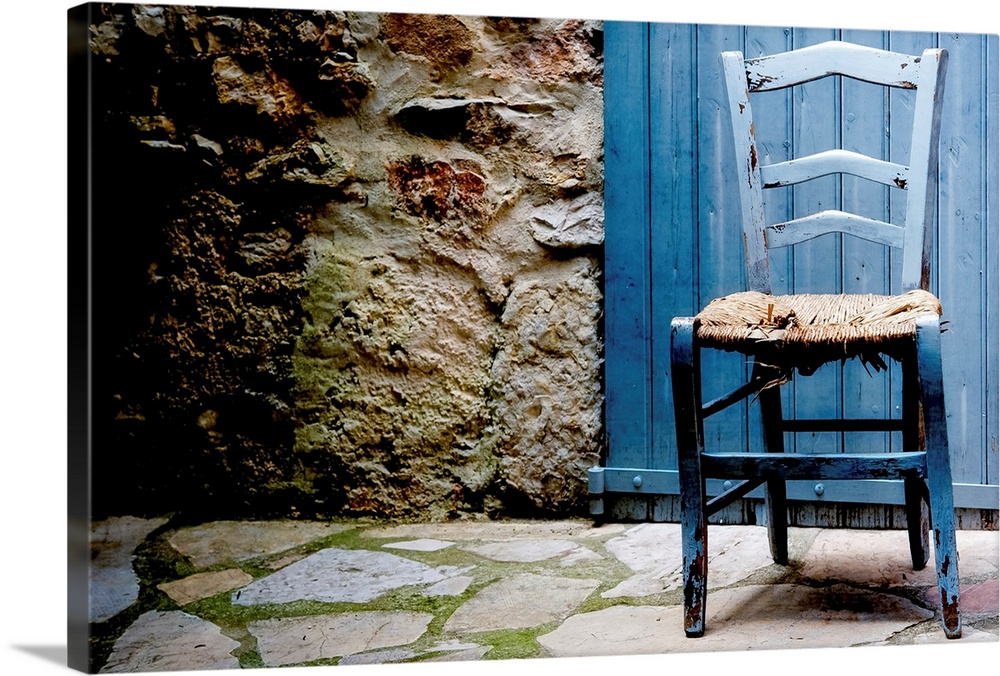 Large Solid-Faced Canvas Print Wall Art Print 30 x 20 entitled Old blue wooden chair with damaged caned seat Solid-Faced Canvas Print entitled Old blue wooden chair with damaged caned seat.  Front capture of old blue wooden chair with damaged caned seat, at doorstep of house with blue wooden door and stone pavement with moss.  Multiple sizes available.  Primary colors within this image include Brown, Black, White, Muted Blue.  Made in the USA.  All products come with a 365 day workmanship guarantee.  Archival-quality UV-resistant inks.  Archival inks prevent fading and preserve as much fine detail as possible with no over-saturation or color shifting.  Canvas is handcrafted and made-to-order in the United States using high quality artist-grade canvas.