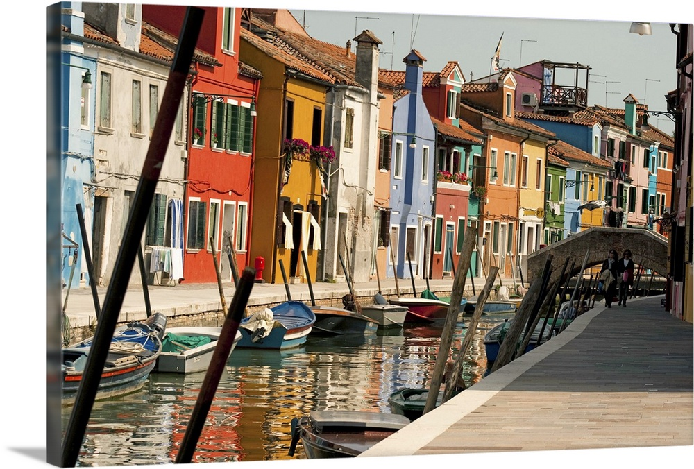 Large Solid-Faced Canvas Print Wall Art Print 30 x 20 entitled Painted houses with reflection in Burano Solid-Faced Canvas Print entitled Painted houses with reflection in Burano.  Italy venice burano island canal water reflection river mediterrenean boat pole ship couple tourist walking sidewalk painted colorful fishermans houses homes frontdoor window penthouse roofs chimney bridge street shadow light sun sunny day sky streetlight window faade.  Multiple sizes available.  Primary colors within this image include Brown, Peach, White, Dark Forest Green.  Made in USA.  Satisfaction guaranteed.  Archival-quality UV-resistant inks.  Archival inks prevent fading and preserve as much fine detail as possible with no over-saturation or color shifting.  Canvas is handcrafted and made-to-order in the United States using high quality artist-grade canvas.
