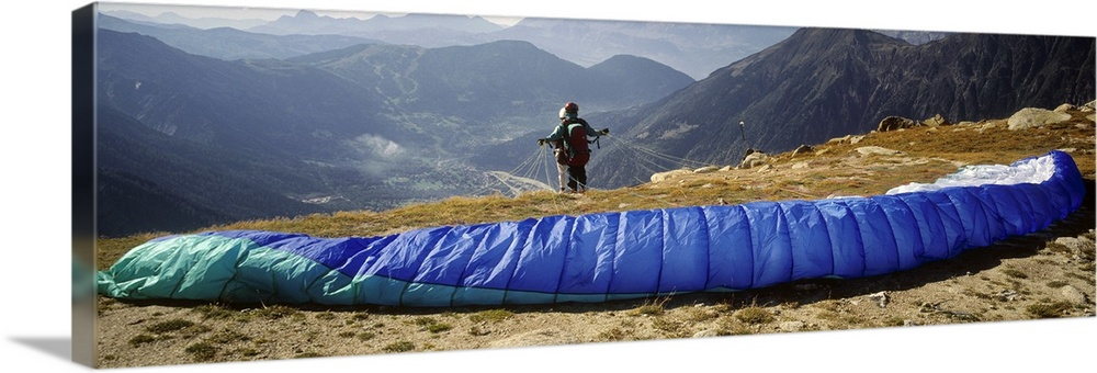 Large Gallery-Wrapped Canvas Wall Art Print 36 x 13 entitled Panoramic view of parachuter on cliff Gallery-Wrapped Canvas entitled Panoramic view of parachuter on cliff.  Multiple sizes available.  Primary colors within this image include Dark Blue Sky Blue Light Gray Muted Blue.  Made in USA.  Satisfaction guaranteed.  Archival-quality UV-resistant inks.  Canvas is acid-free and 20 millimeters thick.  Canvas is designed to prevent fading.