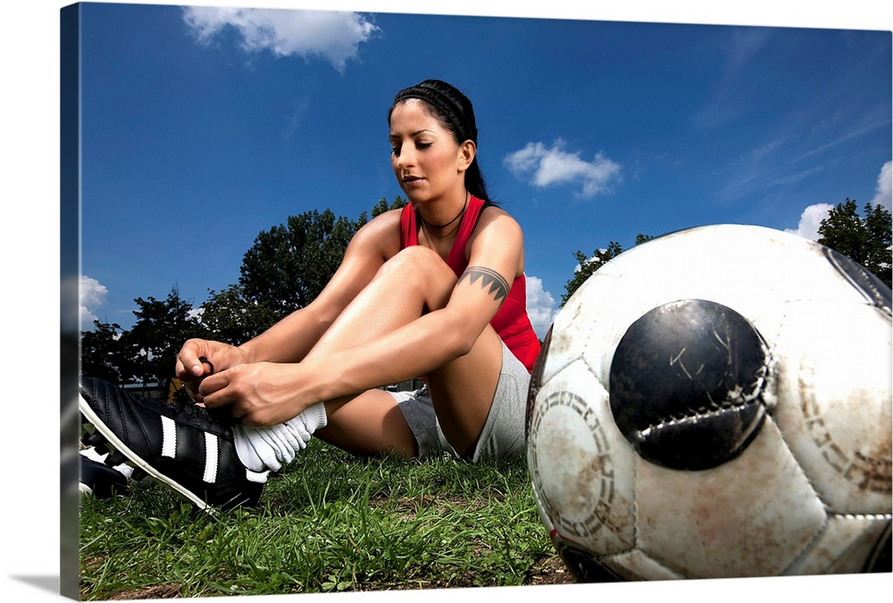 Large Solid-Faced Canvas Print Wall Art Print 30 x 20 entitled Portrait of female football player tying her shoes Solid-Faced Canvas Print entitled Portrait of female football player tying her shoes.  Multiple sizes available.  Primary colors within this image include Dark Red, Peach, Black, White.  Made in the USA.  Satisfaction guaranteed.  Inks used are latex-based and designed to last.  Archival inks prevent fading and preserve as much fine detail as possible with no over-saturation or color shifting.  Featuring a proprietary design, our canvases produce the tightest corners without any bubbles, ripples, or bumps and will not warp or sag over time.