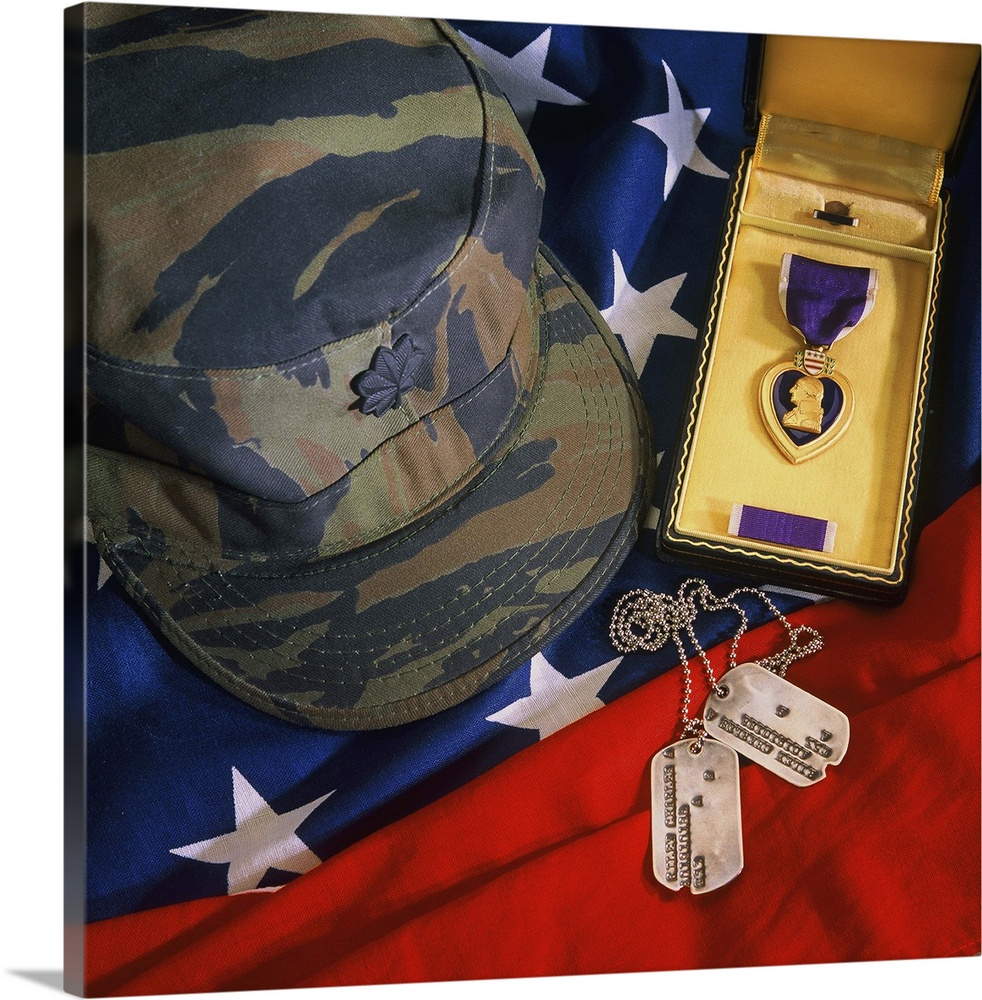 Large Gallery-Wrapped Canvas Wall Art Print 16 x 16 entitled Purple Heart, dog tags, camouflage cap and American flag Gallery-Wrapped Canvas entitled Purple Heart dog tags camouflage cap and American flag.  Medal of honor dog tags camouflage cap and American flag.  Multiple sizes available.  Primary colors within this image include Dark Red Brown Peach Black.  Made in USA.  All products come with a 365 day workmanship guarantee.  Archival-quality UV-resistant inks.  Museum-quality artist-grade canvas mounted on sturdy wooden stretcher bars 1.5 thick.  Comes ready to hang.  Canvases have a UVB protection built in to protect against fading and moisture and are designed to last for over 100 years.