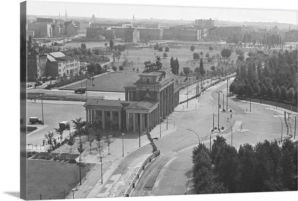 Large Solid-Faced Canvas Print Wall Art Print 36 x 24 entitled Rooftop View Of Brandenburg Gate And Wall, Berlin, Germany,... Solid-Faced Canvas Print entitled Rooftop View Of Brandenburg Gate And Wall, Berlin, Germany, 1961.  8291961-Berlin, Germany- The Brandenburg Gate as seen from top of the Reichstag Building. In center foreground, the wall dividing East and West Berlin. All crowds are held back from this one-time gate into freedom for many East Germans.  Multiple sizes available.  Primary colors within this image include Gray, Silver.  Made in the USA.  Satisfaction guaranteed.  Inks used are latex-based and designed to last.  Featuring a proprietary design, our canvases produce the tightest corners without any bubbles, ripples, or bumps and will not warp or sag over time.  Archival inks prevent fading and preserve as much fine detail as possible with no over-saturation or color shifting.