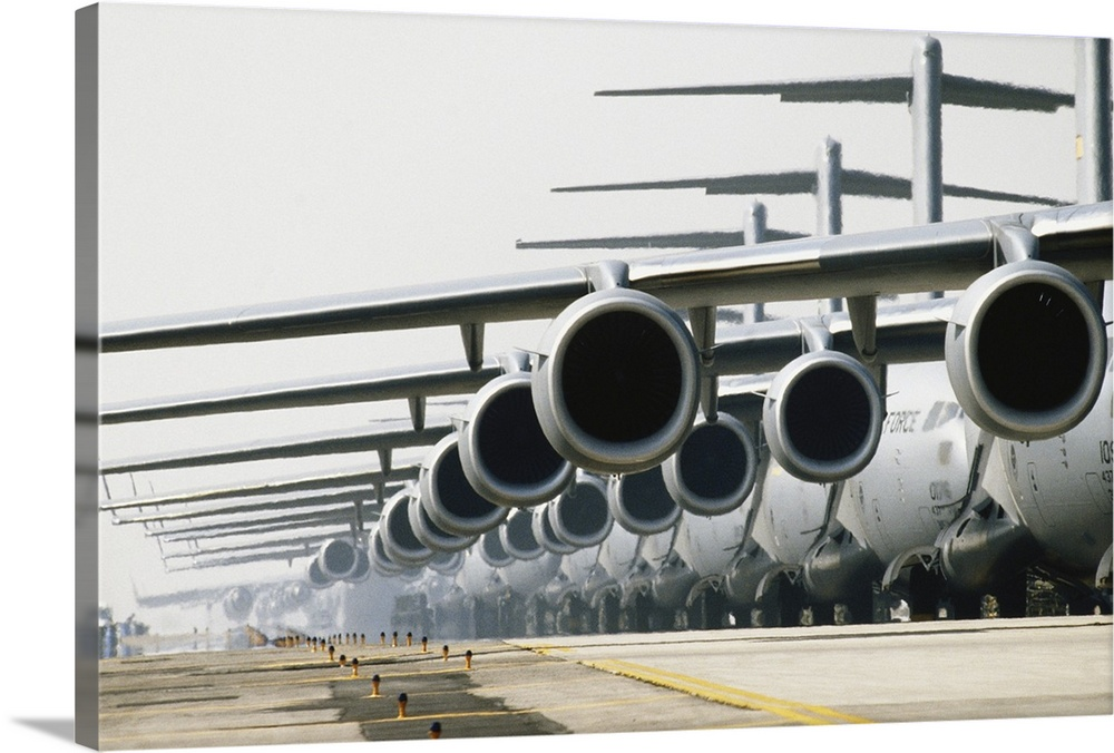Large Solid-Faced Canvas Print Wall Art Print 36 x 24 entitled Row of McDonnell Douglas C-17 Globemaster III planes on runway Solid-Faced Canvas Print entitled Row of McDonnell Douglas C-17 Globemaster III planes on runway.  These Air Force planes are part of Operation Iraqi Freedom and are being used to transport military personnel from air bases in Europe to the Middle East.  Multiple sizes available.  Primary colors within this image include Black, Gray, White.  Made in the USA.  Satisfaction guaranteed.  Inks used are latex-based and designed to last.  Canvas depth is 1.25 and includes a finished backing with pre-installed hanging hardware.  Featuring a proprietary design, our canvases produce the tightest corners without any bubbles, ripples, or bumps and will not warp or sag over time.