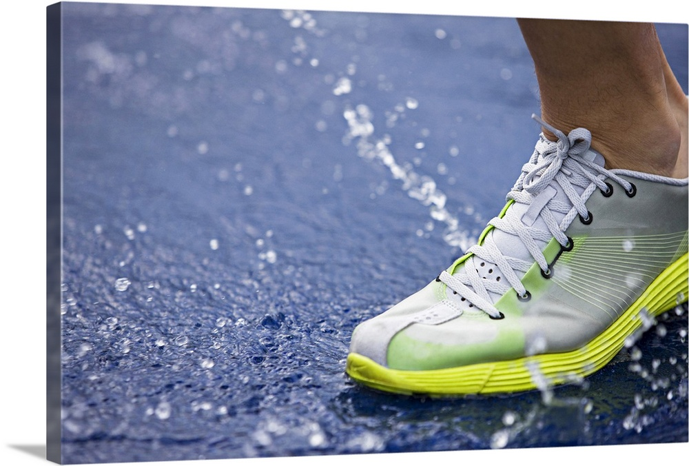 Large Solid-Faced Canvas Print Wall Art Print 30 x 20 entitled Running shoe splashing water on track Solid-Faced Canvas Print entitled Running shoe splashing water on track.  Large canvas photo of an athletic shoe stepping into a water puddle on a track.  Multiple sizes available.  Primary colors within this image include Dark Yellow, Black, Lime Green, Gray Blue.  Made in USA.  Satisfaction guaranteed.  Inks used are latex-based and designed to last.  Archival inks prevent fading and preserve as much fine detail as possible with no over-saturation or color shifting.  Canvas is handcrafted and made-to-order in the United States using high quality artist-grade canvas.