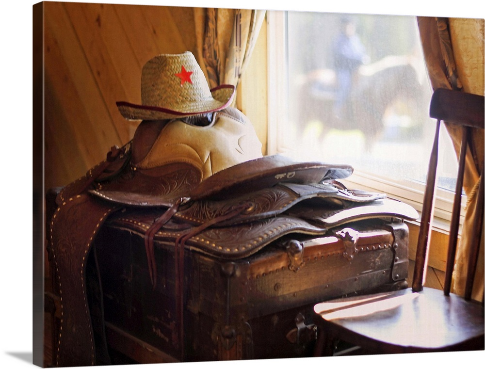 Large Solid-Faced Canvas Print Wall Art Print 40 x 30 entitled Saddle time Solid-Faced Canvas Print entitled Saddle time.  Leather saddle and cowboy hat resting on antique trunk catching the light through a window with out-of-focus horse and rider passing by outdoors.  Multiple sizes available.  Primary colors within this image include Brown, Peach, Black, White.  Made in USA.  Satisfaction guaranteed.  Archival-quality UV-resistant inks.  Archival inks prevent fading and preserve as much fine detail as possible with no over-saturation or color shifting.  Canvas is handcrafted and made-to-order in the United States using high quality artist-grade canvas.