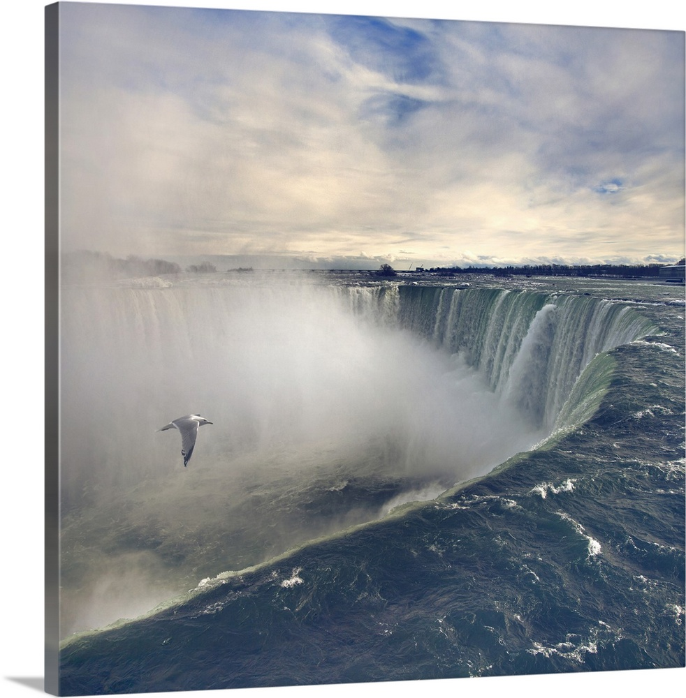 Large Solid-Faced Canvas Print Wall Art Print 20 x 20 entitled Seagull flying over misty Horseshoe Falls in winter time. Solid-Faced Canvas Print entitled Seagull flying over misty Horseshoe Falls in winter time..  Multiple sizes available.  Primary colors within this image include Dark Gray, White.  Made in the USA.  All products come with a 365 day workmanship guarantee.  Archival-quality UV-resistant inks.  Canvas is handcrafted and made-to-order in the United States using high quality artist-grade canvas.  Canvas depth is 1.25 and includes a finished backing with pre-installed hanging hardware.
