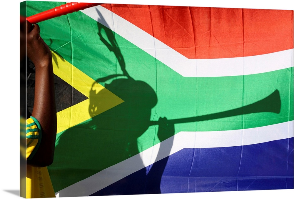 Large Solid-Faced Canvas Print Wall Art Print 30 x 20 entitled Shadow of soccer supporter blowing vuvuzela, South African ... Solid-Faced Canvas Print entitled Shadow of soccer supporter blowing vuvuzela, South African flag in background.  Shadow of soccer supporter blowing vuvuzela, South African flag in background, Johannesburg, South Africa.  Multiple sizes available.  Primary colors within this image include Brown, Pink, Black, White.  Made in USA.  All products come with a 365 day workmanship guarantee.  Inks used are latex-based and designed to last.  Canvas depth is 1.25 and includes a finished backing with pre-installed hanging hardware.  Canvas is handcrafted and made-to-order in the United States using high quality artist-grade canvas.