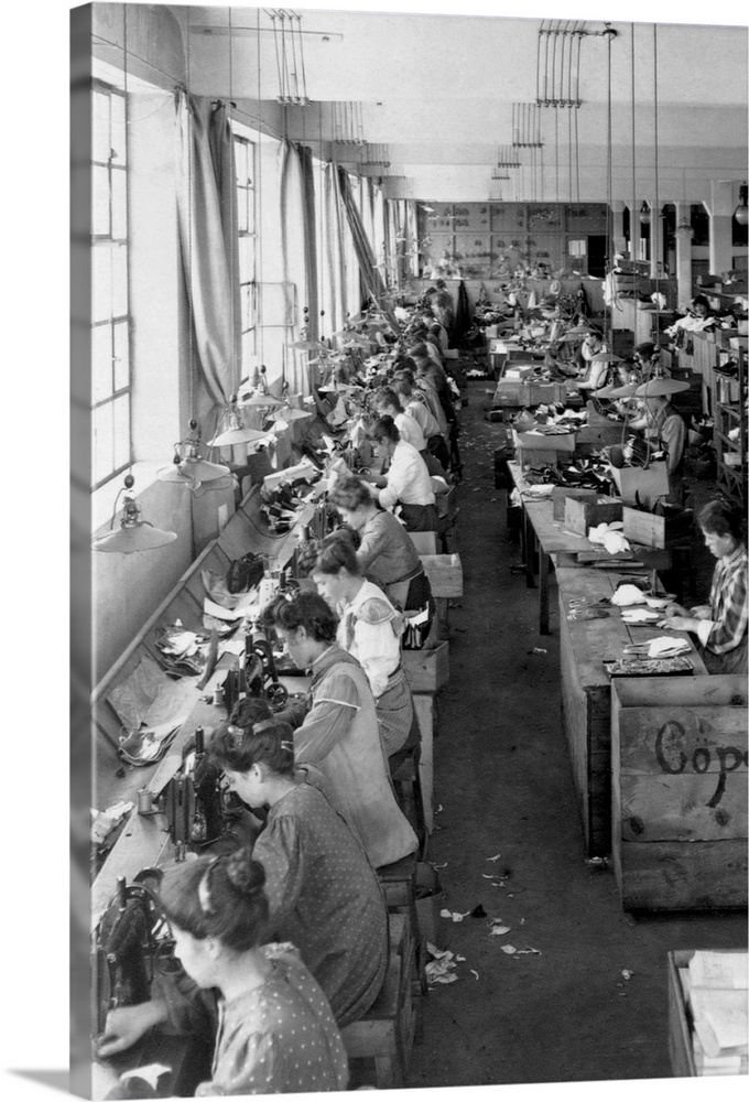 Large Solid-Faced Canvas Print Wall Art Print 20 x 30 entitled Shoe Factory Workers Solid-Faced Canvas Print entitled Shoe Factory Workers.  Shoe factory workers sewing on long tables.  Multiple sizes available.  Primary colors within this image include Dark Gray, Silver.  Made in the USA.  Satisfaction guaranteed.  Inks used are latex-based and designed to last.  Canvas depth is 1.25 and includes a finished backing with pre-installed hanging hardware.  Archival inks prevent fading and preserve as much fine detail as possible with no over-saturation or color shifting.