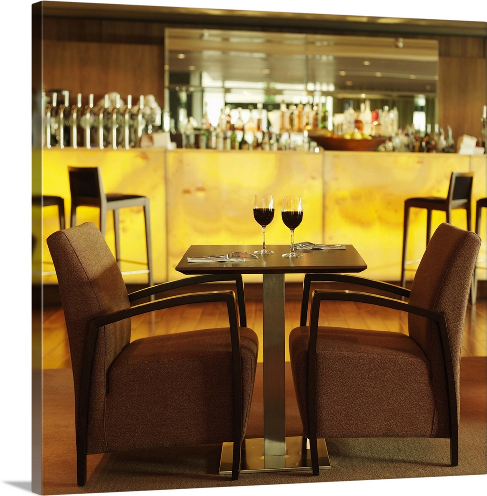 Large Solid-Faced Canvas Print Wall Art Print 20 x 20 entitled Side view of table and chair in hotel bar Solid-Faced Canvas Print entitled Side view of table and chair in hotel bar.  Multiple sizes available.  Primary colors within this image include Peach, Light Yellow, Dark Gray, White.  Made in the USA.  All products come with a 365 day workmanship guarantee.  Inks used are latex-based and designed to last.  Archival inks prevent fading and preserve as much fine detail as possible with no over-saturation or color shifting.  Canvas is handcrafted and made-to-order in the United States using high quality artist-grade canvas.