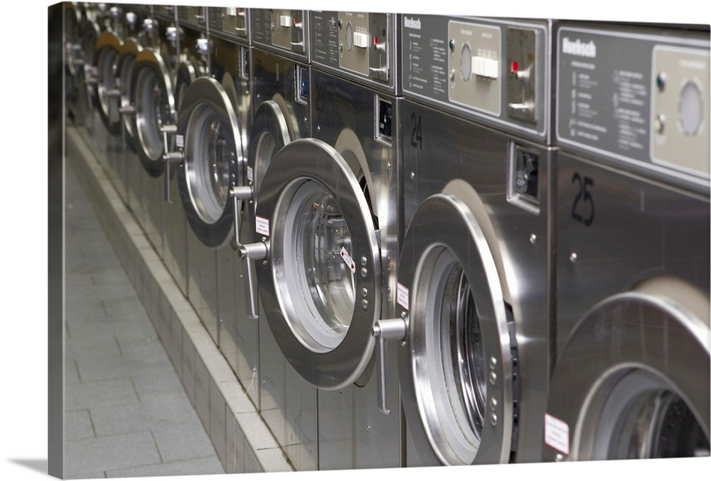 Large Solid-Faced Canvas Print Wall Art Print 30 x 20 entitled Silver washing machines at a city laundromat Solid-Faced Canvas Print entitled Silver washing machines at a city laundromat.  Silver washing machines at a city laundrette.  Multiple sizes available.  Primary colors within this image include Black, Gray, White.  Made in USA.  Satisfaction guaranteed.  Archival-quality UV-resistant inks.  Featuring a proprietary design, our canvases produce the tightest corners without any bubbles, ripples, or bumps and will not warp or sag over time.  Canvas depth is 1.25 and includes a finished backing with pre-installed hanging hardware.