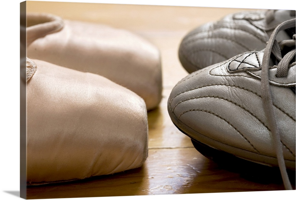 Large Solid-Faced Canvas Print Wall Art Print 30 x 20 entitled still life of ballet shoes and soccer cleats Solid-Faced Canvas Print entitled still life of ballet shoes and soccer cleats.  Photograph of the tips of ballet point shoes facing the tips of football cleats on a hardwood floor.  Multiple sizes available.  Primary colors within this image include Brown, Black, Gray, White.  Made in the USA.  Satisfaction guaranteed.  Inks used are latex-based and designed to last.  Archival inks prevent fading and preserve as much fine detail as possible with no over-saturation or color shifting.  Featuring a proprietary design, our canvases produce the tightest corners without any bubbles, ripples, or bumps and will not warp or sag over time.