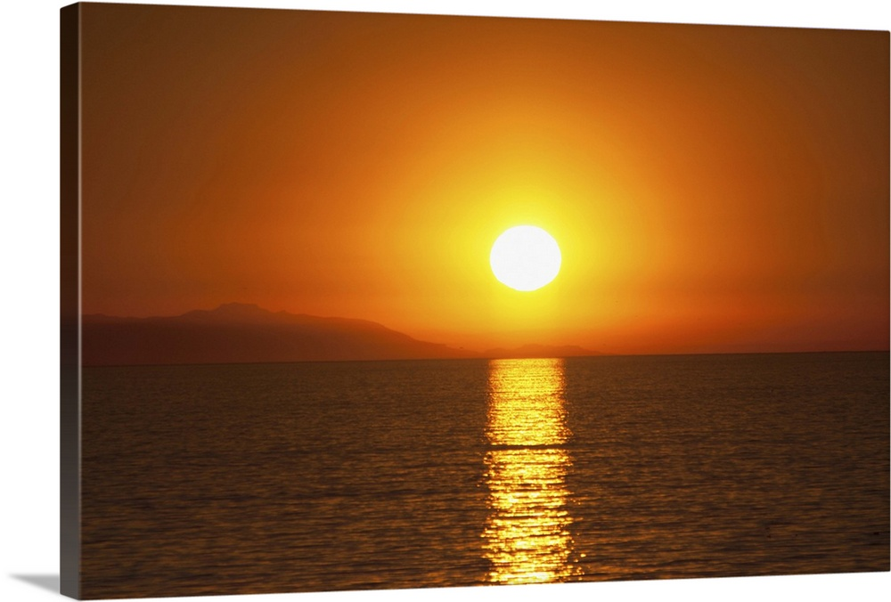 Large Gallery-Wrapped Canvas Wall Art Print 24 x 16 entitled Sunset over Santa Catalina Island Gallery-Wrapped Canvas entitled Sunset over Santa Catalina Island.  Scenic dark orange sunset over Santa Catalina Island off the coast of California as seen from the Huntington Beach Pier in Huntington Beach California.  The reflection of the sun cuts a bold swath in the dark water towards the camera.  Multiple sizes available.  Primary colors within this image include Yellow Brown Dark Gray White.  Made in USA.  All products come with a 365 day workmanship guarantee.  Inks used are latex-based and designed to last.  Canvas frames are built with farmed or reclaimed domestic pine or poplar wood.  Canvases have a UVB protection built in to protect against fading and moisture and are designed to last for over 100 years.