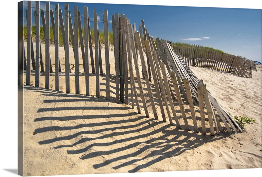 Large Solid-Faced Canvas Print Wall Art Print 30 x 20 entitled The low sun casts long shadows of a wooden fence on a sandy... Solid-Faced Canvas Print entitled The low sun casts long shadows of a wooden fence on a sandy dune by the ocean..  Multiple sizes available.  Primary colors within this image include Dark Yellow, Peach, Gray.  Made in the USA.  Satisfaction guaranteed.  Inks used are latex-based and designed to last.  Canvas is handcrafted and made-to-order in the United States using high quality artist-grade canvas.  Canvas depth is 1.25 and includes a finished backing with pre-installed hanging hardware.