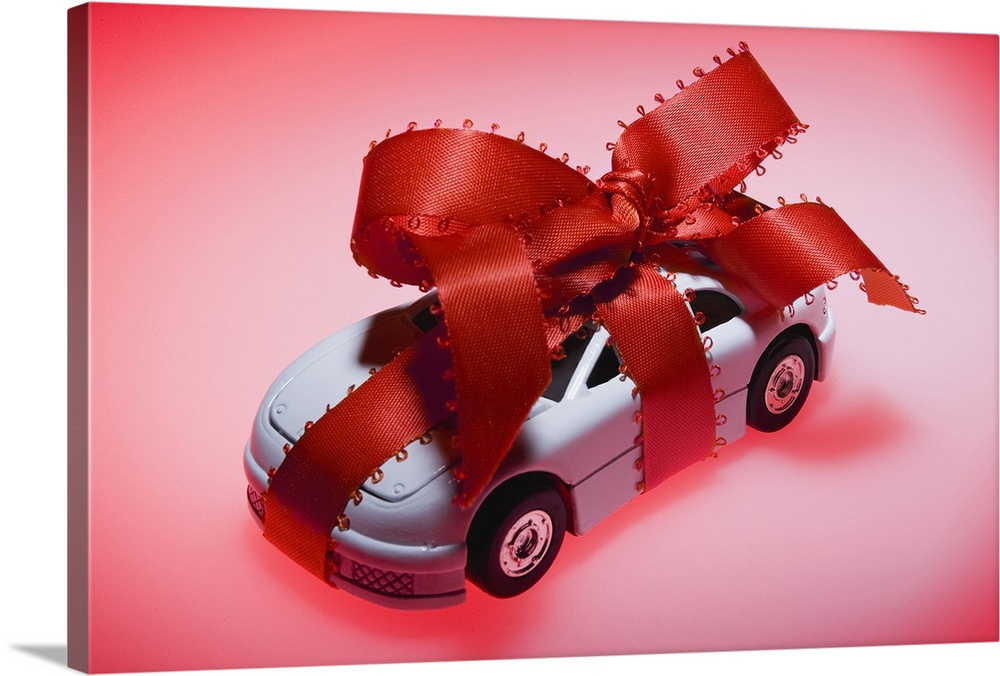 Large Solid-Faced Canvas Print Wall Art Print 30 x 20 entitled Toy car wrapped in ribbon Solid-Faced Canvas Print entitled Toy car wrapped in ribbon.  Multiple sizes available.  Primary colors within this image include Dark Red, Pink, Dark Gray.  Made in USA.  All products come with a 365 day workmanship guarantee.  Inks used are latex-based and designed to last.  Canvas is handcrafted and made-to-order in the United States using high quality artist-grade canvas.  Archival inks prevent fading and preserve as much fine detail as possible with no over-saturation or color shifting.