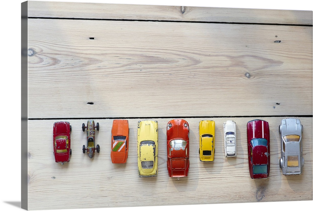Large Solid-Faced Canvas Print Wall Art Print 30 x 20 entitled Toy cars lined up in a row on floor Solid-Faced Canvas Print entitled Toy cars lined up in a row on floor.  Multiple sizes available.  Primary colors within this image include Yellow, Dark Red, Pink, Silver.  Made in USA.  Satisfaction guaranteed.  Archival-quality UV-resistant inks.  Canvas is handcrafted and made-to-order in the United States using high quality artist-grade canvas.  Featuring a proprietary design, our canvases produce the tightest corners without any bubbles, ripples, or bumps and will not warp or sag over time.