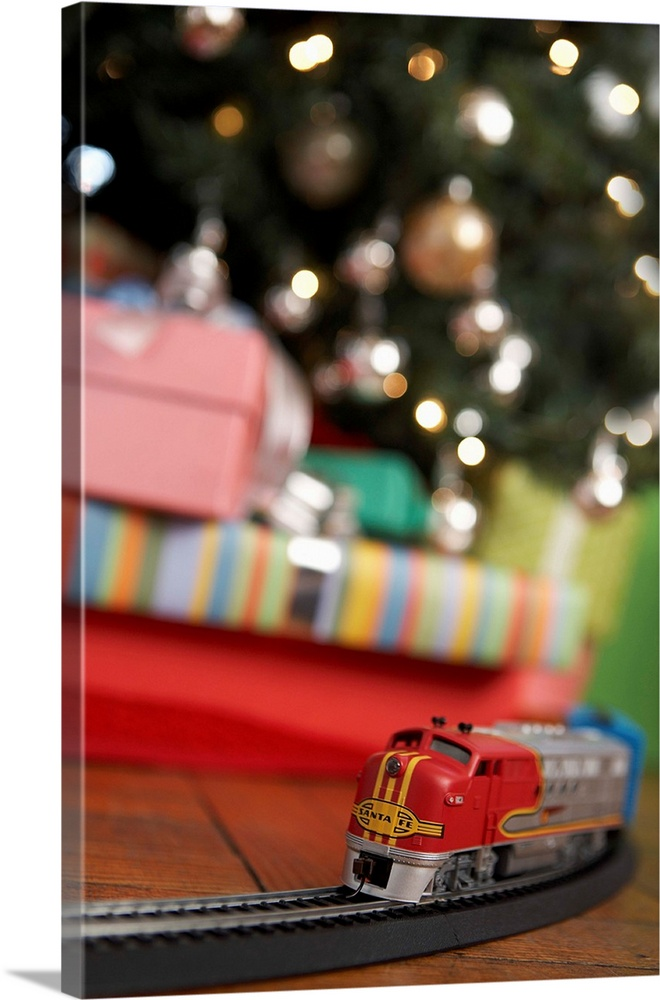 Large Solid-Faced Canvas Print Wall Art Print 20 x 30 entitled Toy Train Running Beneath Christmas Tree Solid-Faced Canvas Print entitled Toy Train Running Beneath Christmas Tree.  Multiple sizes available.  Primary colors within this image include Dark Red, Peach, Black.  Made in the USA.  Satisfaction guaranteed.  Inks used are latex-based and designed to last.  Archival inks prevent fading and preserve as much fine detail as possible with no over-saturation or color shifting.  Canvas is handcrafted and made-to-order in the United States using high quality artist-grade canvas.